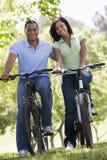 Couple on bikes outdoors smiling Royalty Free Stock Photo