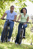 Couple on bikes outdoors smiling Royalty Free Stock Photos