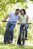 Couple on bikes outdoors smiling Stock Image