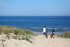 Couple with bikes on a sandy beach by the ocean Stock Images