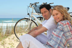 Couple with bikes. Sitting on the sand dunes stock photos