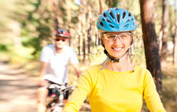 Couple on bikes in the sunny forest Stock Image
