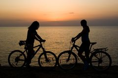 Couple with bikes watching sunset. Stock Photography