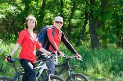 Couple biking. Two cyclists relax biking outdoors royalty free stock photos