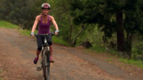 Couple biking through a forest. In the countryside stock footage