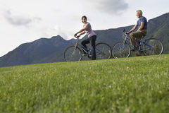 Couple Biking On Grass Against Mountain Range. Side view of a middle aged men and women biking on landscape with mountain range in the background Royalty Free Stock Photos
