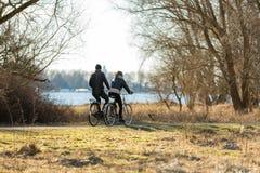 Couple biking in park `de Oeverlanden` in Amsterdam. Royalty Free Stock Photos