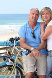 Couple biking by the seashore. Royalty Free Stock Photo