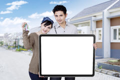 Couple with billboard and keys of new house Royalty Free Stock Photography