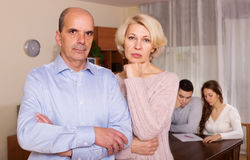 Couple with  bills at table and senior parents apart Royalty Free Stock Photo