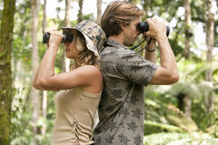 Couple with Binoculars. Man and women back to back, looking through binoculars in the forest Stock Photography