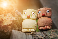 Couple birds, two wise owls statues in garden with warm light flare Stock Images