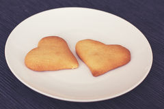 A couple of biscuit hearts. Two biscuit hearts on a plate Stock Images