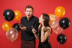 Couple in black clothes hold cellphone celebrating birthday holiday party isolated on bright red background air balloons stock photos