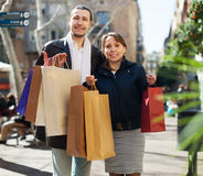 Couple in black jackets with purchases Stock Photos