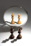 A couple of a black king and queen is looking in a mirror to see themselves as a white couple. A pair of a black king and a black queen chess piece stands in Stock Photo