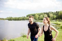 Couple jogging outdoors. Couple in black sportswear running near the lake during the morning exercise Royalty Free Stock Image