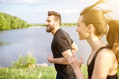 Couple jogging outdoors. Couple in black sportswear running near the lake during the morning exercise Royalty Free Stock Photos