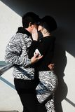 Couple in black and zebra print clothes kissing in a shadow. Young couple in black and zebra print clothes kissing in a shadow royalty free stock photography