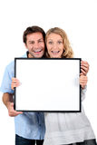 Couple with blank picture frame Stock Photos