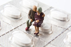 Couple with blister pack. Miniature elderly couple sitting on a blister pack of white pills Stock Photography