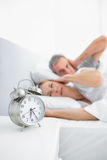 Couple blocking their ears from alarm clock noise Stock Image