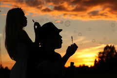 Couple with blow bubbles at sunset Royalty Free Stock Photo