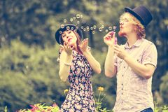 Couple blowing bubbles outdoor. Happy funny hipster couple playing together blowing soap bubbles outdoor in spring park stock photos