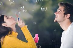 Couple blowing bubbles, outdoors. Young couple blowing bubbles, outdoors Stock Photo