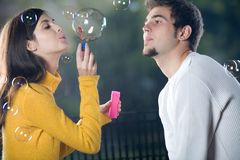 Couple blowing bubbles, outdoors. Young couple blowing bubbles, outdoors Royalty Free Stock Photography