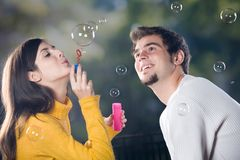 Couple blowing bubbles, outdoors. Young couple blowing bubbles, outdoors Royalty Free Stock Photo