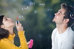 Couple blowing bubbles, outdoors. Young couple blowing bubbles, outdoors Royalty Free Stock Image