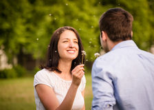 Couple blowing dandelions Royalty Free Stock Photos