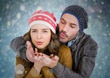 Couple blowing kisses against blue bokeh background Stock Photos