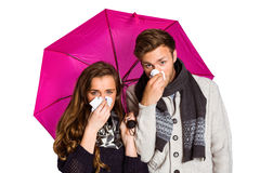 Couple blowing nose while holding umbrella Royalty Free Stock Image