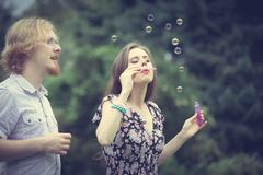 Couple blowing soap bubbles, having fun royalty free stock images