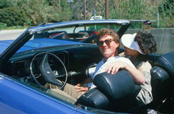 A couple in a blue Buick Electra convertible Stock Images