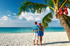Couple in blue clothes on a beach at christmas. Couple in blue clothes on a tropical beach at christmas Royalty Free Stock Photos