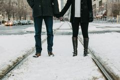 Couple Blue Denim Jeans Holding Hands With Person Black Sweat Pants With Black Knee High Boots Standing in Road With Snow Stock Images