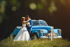Couple by Blue Old Car. Hugging couple with bouquet at blue old car Stock Photos
