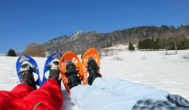 Couple with blue and orange snowshoes in the mountains Stock Photo