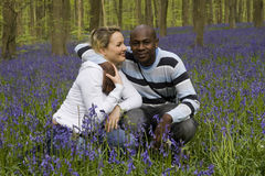Couple in bluebells. Young happy ethnically diverse couple in nature Stock Photos