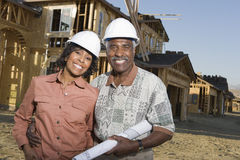 Couple With Blueprint In Front Of Incomplete House. Portrait of happy senior African American couple with blueprint in front of house under construction Stock Images