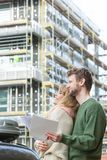 Couple with blueprint project keys on construction site. Real estate and family concept - young couple on front of new big modern house construction site with Royalty Free Stock Photo