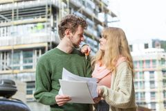 Couple with blueprint project keys on construction site. Real estate and family concept - young couple on front of new big modern house construction site with Royalty Free Stock Photos