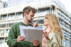 Couple with blueprint project keys on construction site. Real estate and family concept - young couple on front of new big modern house construction site with Stock Images