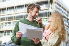 Couple with blueprint project keys on construction site Stock Photos