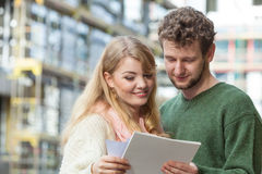 Couple with blueprint project keys on construction site Stock Image