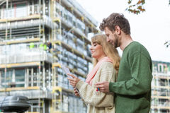 Couple with blueprint project keys on construction site Stock Photography