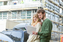 Couple with blueprint project keys on construction site. Real estate and family concept - young couple on front of new big modern house construction site with Royalty Free Stock Images